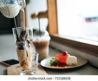 Milk is poured into coffee ice with strawberry cheesecake on background  in cafe