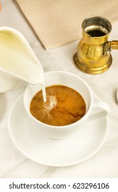 Milk poured into a cup of coffee, with a vintage coffee pot in the background. Selective focus, place for text