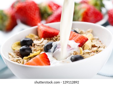 milk pouring into bowl of cereals with fresh berries