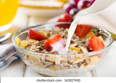 milk pouring into bowl of cereals