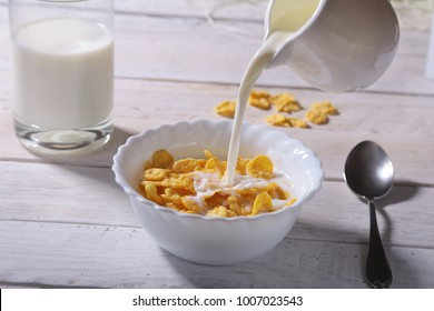 Milk pouring into a bowl of delicious corn flake cereals and cap with espresso coffee. Morning breakfast.