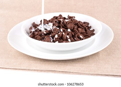Milk pouring into a dish with chocolate cereal flakes.