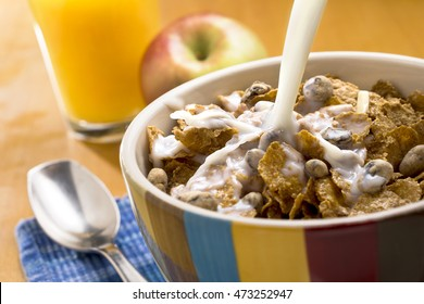 Milk pouring over a bowl of cereal with a spoon, apple and orange juice in the background.