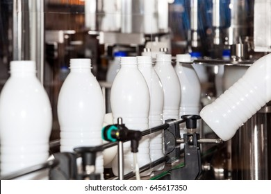 Milk production line. Milk bottles on industrial conveyor