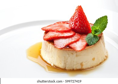 Milk pudding with caramel and strawberries on a white plate