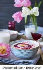 Milk rice porridge with raspberry jam and butter