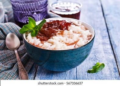 Milk rice porridge with strawberry jam. Selective focus.
