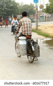 The milk seller is carrying the cans on a bicycle in India street. India, Govardhan, November 2016