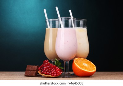 Milk shakes with fruits and chocolate on wooden table on blue background