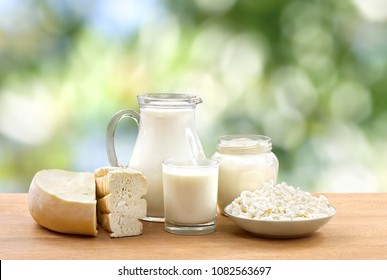 Milk, sour cream, cheese and cottage cheese on wooden table on defocused of natural background with space for text