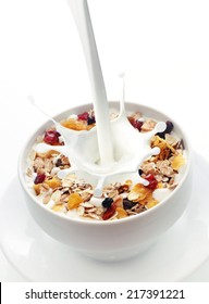 Milk splashing into a bowl of fresh muesli with a mix of wheat, oats and bran with dried fruit and nuts over white with copyspace