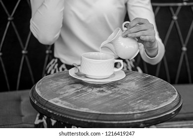 With milk tastes better. Tips for healthier coffee drinking. Hand female adding pouring milk to black coffee outdoors cafe terrace, close up. Mug americano or black coffee and jug with milk.