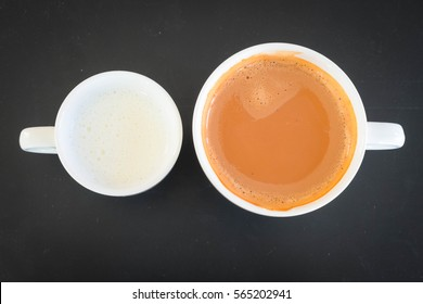 Milk and tea in black background