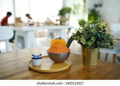 Milk tea kakigori - Thai tea shaved ice topped with egg yolk floss and glutinous rice balls (Bua Loi), served with condensed milk. Trendy dessert in Thailand.