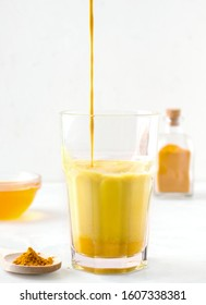 milk tea with turmeric and honey on a white background