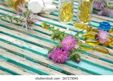 Milk thistle blossoms on an old wooden surface.Milk thistle oil in softgels in the background