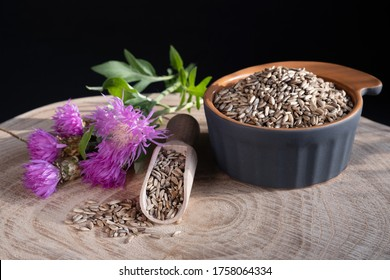 Milk thistle (Silybum marianum) seeds in wooden spoon and ceramic bowl, flowers on a wooden background. Medical plants. Alternative medicine.