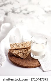 Milk in a transparent glass and healthy cookies with cereals on a cork wood stand. On a marble background.