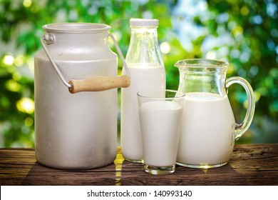 Milk in various dishes on the old wooden table in an outdoor setting. Dairy concept.