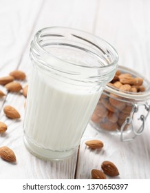 Milk or yogurt in mason jar on white wooden table with almonds in airtight conainer aside