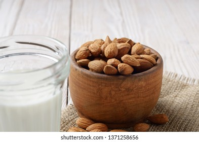Milk or yogurt in mason jar on white wooden table with bowl of almonds on hemp napkin aside