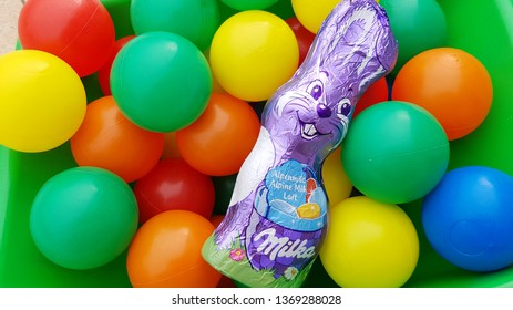 Milka chocolate Easter bunny with a lot of coloured balls on background