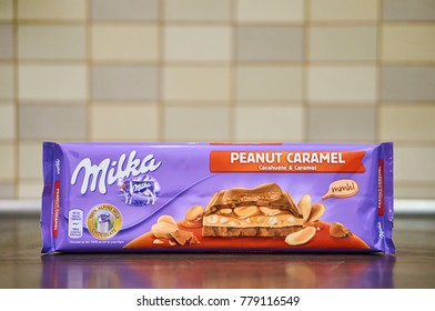 Milka Peanut Caramel chocolate in a large pack on wooden table on December 2017 in Poznan, Poland
