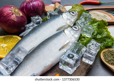 Milkfish or bangus with spices for cooking on table., Top view Fresh raw fish and food ingredients on table,