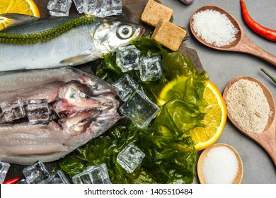 Milkfish or bangus with spices for cooking on table., Top view Fresh raw fish and food ingredients on table