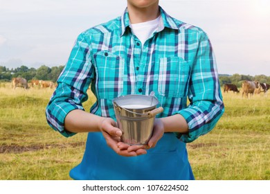 Milkmaid with a pail of milk on the background of the pasture.