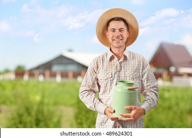 Milkman with watering can on blurred dairy farm background