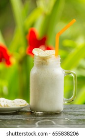 Milkshake with banana in a glass on wood table and soft background.