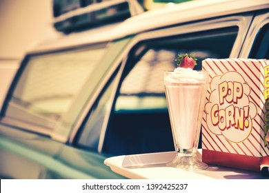 Milkshake and popcorn on a tray attached to a vintage car