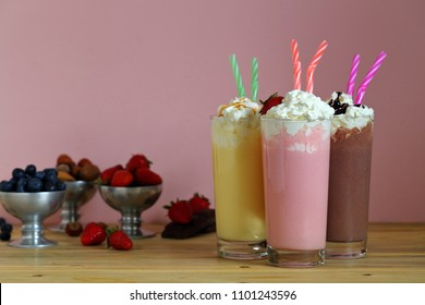 milkshake with strawberries chocolate and vanilla in glass kitchen table background