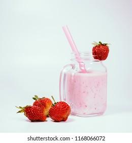 Milkshake with strawberries on white background.