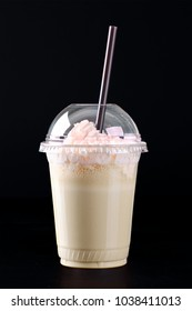 Milkshake with whipped cream in a clear plastic glass