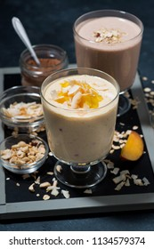 milkshakes with chocolate, oatmeal and mango in glasses, vertical top view