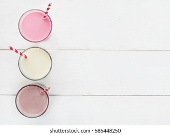 Milkshakes with chocolate, strawberry, banana flavor on a white wooden background