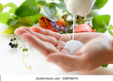 milky lotion with herbs in background