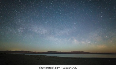 Milky Way above horizon across the lake with mountains range in the background