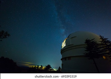 The milky way above a large refractor telescope with open bay window to observe stars.  Astronomers at work.