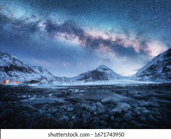 Milky Way above snow covered mountains and stone beach in winter at night in Lofoten Islands, Norway. Arctic landscape with blue starry sky,  sea coast, snowy rocks, galaxy. Beautiful space and nature