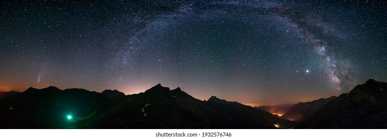 Milky Way arc and stars in night sky over the Alps. Outstanding Comet Neowise glowing at the horizon on the left. Panoramic view, astro photography, stargazing.