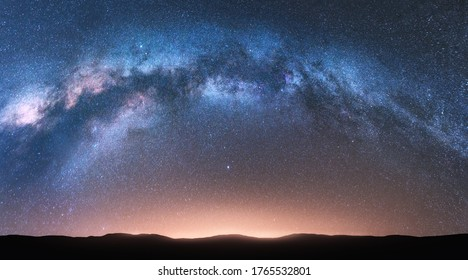 Milky Way arch. Fantastic night landscape with bright arched milky way, sky with stars, yellow sunlight and hills. Beautiful scene with universe. Space background with starry sky. Galaxy and nature