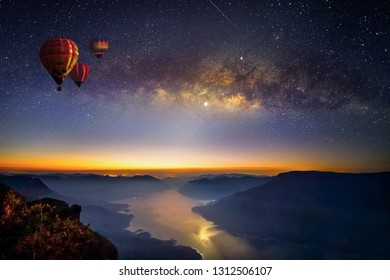 Milky way and balloons before sunrise on view point with long exposure photograph, with grain at Pha daeng Luang Viewpoint, Mae Ping Nation Park, Lumphun, Thailand
