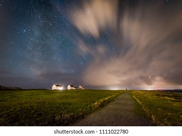 Milky way behind clouds over farm Norway