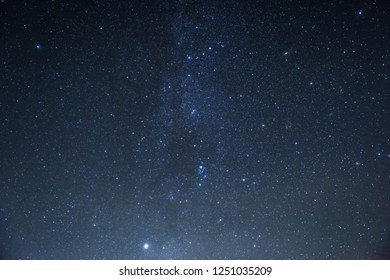 Milky way at center. Photo of beautiful blue night sky filled with stars.