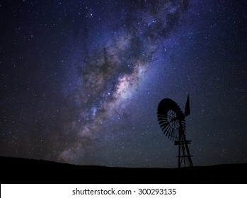 The milky way core rises above a windmill in the Karoo desert, South Africa.