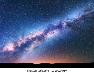 Milky Way. Fantastic night landscape with purple milky way, sky full of stars, yellow light and hills. Shiny stars. Beautiful scene with universe. Space background with starry sky. Astrophotography.