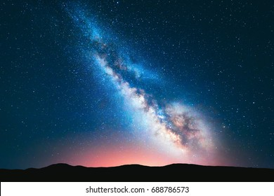Milky Way. Fantastic night landscape with bright milky way, sky full of stars, yellow light and hills. Shiny stars. Picturesque scene with our universe. Space background. Amazing astrophotography